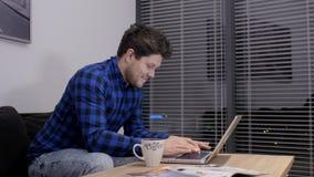 Glimlachende zakenman die aan laptop bij een bureau tijdens recente uren werken stock footage