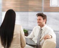 Glimlachende zakenman die aan vrouw spreekt Stock Foto