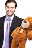 Glimlachende zakenman die een teddybeer geeft stock fotografie