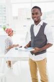 Glimlachende zakenman die en notitieboekje bevinden zich houden Royalty-vrije Stock Afbeelding