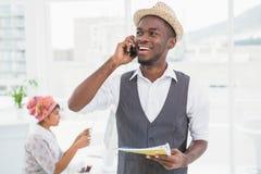 Glimlachende zakenman die en notitieboekje telefoneren houden Royalty-vrije Stock Afbeeldingen
