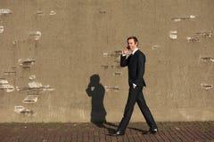 Glimlachende zakenman die en op mobiele telefoon lopen spreken Royalty-vrije Stock Afbeelding