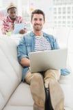 Glimlachende zakenman die laptop op laag met behulp van Stock Foto