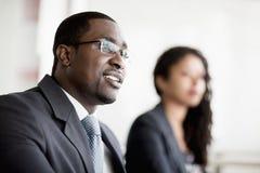 Glimlachende zakenman die op een commerciële vergadering luisteren Stock Afbeeldingen