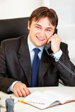 Glimlachende zakenman die op telefoon in bureau spreekt Stock Afbeelding