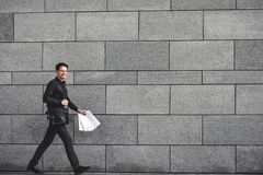 Glimlachende zakenman die snel met aktentas bij stad lopen stock afbeelding
