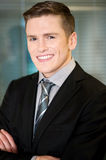Glimlachende zakenman die vol vertrouwen stellen Stock Foto's