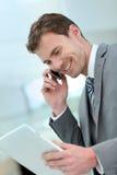Glimlachende zakenman die zaken op telefoon doen royalty-vrije stock foto
