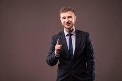 Glimlachende zakenman die zich met een grijnslach en een opgeheven indexvin bevinden royalty-vrije stock fotografie