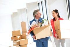 Glimlachende zakenman en onderneemster die elkaar bekijken terwijl het dragen van kartondozen in nieuw bureau Royalty-vrije Stock Afbeeldingen