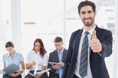 Glimlachende zakenman en zijn medewerkers Royalty-vrije Stock Afbeelding