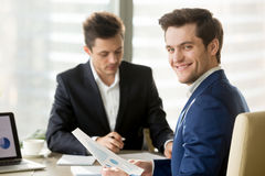 Glimlachende zakenman, financieel analist of voorraadmakelaar die a kijken stock afbeeldingen