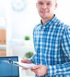 Glimlachende zakenman met rode omslagzitting in het bureau Stock Afbeelding