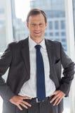 Glimlachende zakenman met zijn handen op heupen royalty-vrije stock afbeeldingen