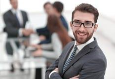 Glimlachende zakenman op achtergrond van bureau stock foto's