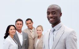 Glimlachende zakenman voor zijn team stock afbeeldingen