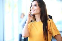 Glimlachende zekere bedrijfsvrouw die een telefoongesprek hebben stock foto