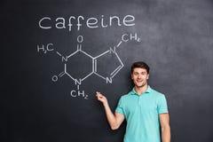 Glimlachende zekere jonge student die chemische structuur van cafeïnemolecule tonen Stock Fotografie