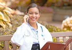Glimlachende zekere vrouwelijke artsenberoepsbeoefenaar die op telefoon spreken stock fotografie