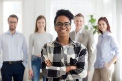 Glimlachende zekere zwarte bedrijfwerknemer die zich met collega's bij achtergrond bevinden stock afbeelding