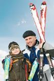 Glimlachende zoon en vader met skis bij Stock Afbeeldingen