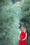 Glimlachende zwangere vrouw die neer kijken royalty-vrije stock afbeeldingen