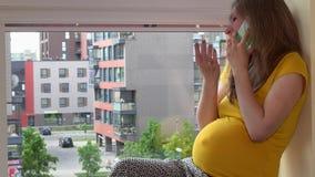 Glimlachende zwangere vrouw die op haar smartphonezitting spreken op venstervensterbank stock footage
