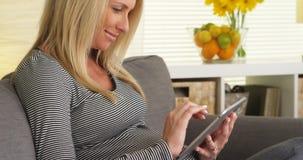 Glimlachende zwangere vrouw die tablet gebruiken stock foto's