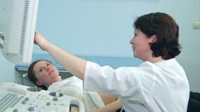 Glimlachende zwangere vrouw die ultrasone klankresultaten bekijken met arts stock videobeelden