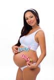 Glimlachende zwangere vrouw met etiketbaby voor pasgeboren meisje, jongen of tweelingen Gelukkige zwangerschap Royalty-vrije Stock Afbeelding