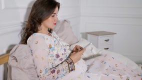 Glimlachende zwangere vrouw wat zitting op bed en het gebruiken van smartphone in huis stock videobeelden