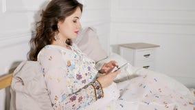 Glimlachende zwangere vrouw wat zitting op bed en het gebruiken van smartphone in huis royalty-vrije stock foto