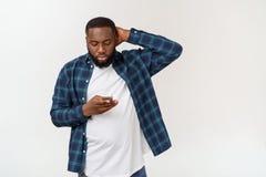Glimlachende zwarte jonge mens die in glazen telefoon houden bekijkend geïsoleerd smartphone op witte grijze studioachtergrond royalty-vrije stock afbeeldingen