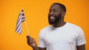 Glimlachende zwarte mens die de vlag van Griekenland, internationaal vriendschapsconcept, close-up golven stock videobeelden