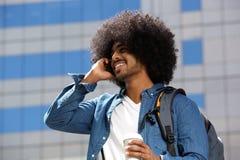 Glimlachende zwarte mens die met afro mobiele telefoon in de stad met behulp van Stock Foto's
