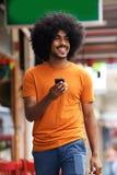 Glimlachende zwarte mens die met cellphone lopen Royalty-vrije Stock Foto's