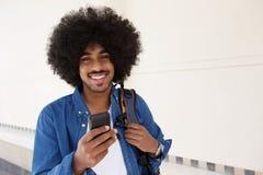 Glimlachende zwarte mens die met celtelefoon lopen Stock Fotografie