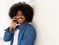 Glimlachende zwarte mens die op mobiele telefoon luisteren Royalty-vrije Stock Foto