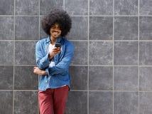 Glimlachende zwarte mens die zich met mobiele buiten telefoon bevinden Stock Fotografie