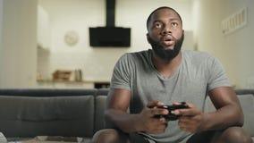 Glimlachende zwarte mens het spelen videospelletje thuis keuken stock video