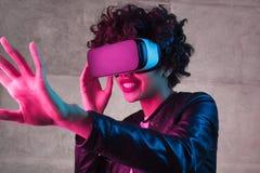 Glimlachende zwarte tiener die met virtuele werkelijkheid interactie aangaan stock fotografie