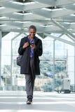 Glimlachende zwarte zakenman die met celtelefoon bij luchthaven lopen Stock Foto