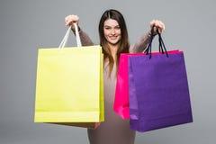 Glimlachklant die kleding dragen die lege kleurrijke het winkelen zakken tonen en het richten van u op grijze achtergrond Royalty-vrije Stock Afbeelding