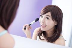Glimlachvrouw met make-upborstels Stock Afbeeldingen