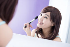 Glimlachvrouw met make-upborstels Stock Afbeelding