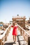 Glimlachvrouw in witte hoed en zonnebril die zich op houten pijler bevinden De zomerroeping stock foto