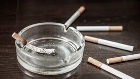 Glimma brännskador för en cigarett i ett askfat på en tabell arkivbilder