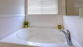 Glimma vitt badkar för panoramaram inom ett badrum med en stor spegel på väggen arkivbilder