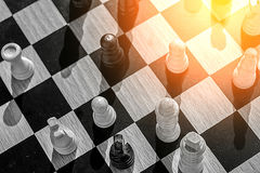 A glimmer of hope and warm sun in the corner of this chess battl Stock Image
