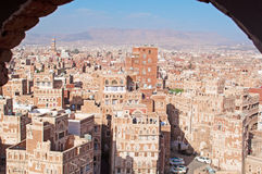 A glimpse of decorated houses and palaces behind arch wall in the Old City of Sana'a, Yemen Stock Photo